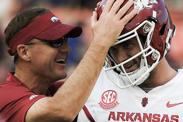 Arkansas coach Chad Morris (left) talks with quarterback Ty Storey prior to a game against Auburn on Saturday, Sept. 22, 2018, in Auburn, Ala.
