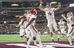 Arkansas players, including quarterback Ty Storey (4) and wide receiver Mike Woods (8) celebrate after a touchdown pass to Woods in the fourth quarter of a game against Texas A&M on Saturday, Sept. 29, 2018, during the Southwest Classic at AT&T Stadium in Arlington, Texas.
