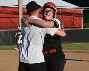 RICK PECK/SPECIAL TO MCDONALD COUNTY PRESS McDonald County's Kylie Helm celebrates with assistant coach Kyle Smith after knocking in the winning run in the Lady Mustangs' 3-2 win over Logan-Rogersville on Sept. 27 at MCHS.