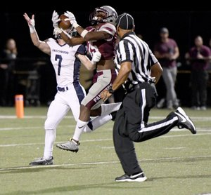 Bud Sullins/Special to Siloam Sunday Siloam Springs senior wide receiver Primo Agbehi hauls in a 53-yard touchdown pass from Landon Ellis as Greenwood's Dawson James defends on the play during Friday's game at Panther Stadium. Greenwood defeated Siloam Springs 42-7.