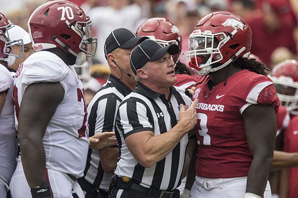 An official separates Arkansas defensive end McTelvin Agim and Alabama offensive lineman Alex Leatherwood after a play in the second quarter of a game Saturday, Oct. 6, 2018, at Razorback Stadium in Fayetteville.