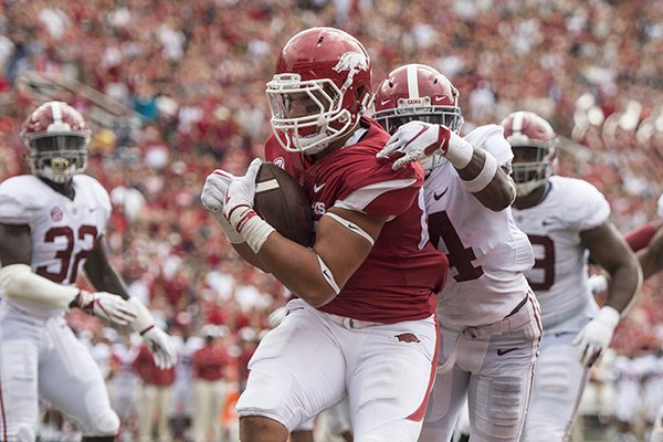 Arkansas tight end Cheyenne O'Grady reels in a touchdown pass under pressure from Alabama safety Deionte Thompson in the second quarter of a game Saturday, Oct. 6, 2018, at Razorback Stadium in Fayetteville.