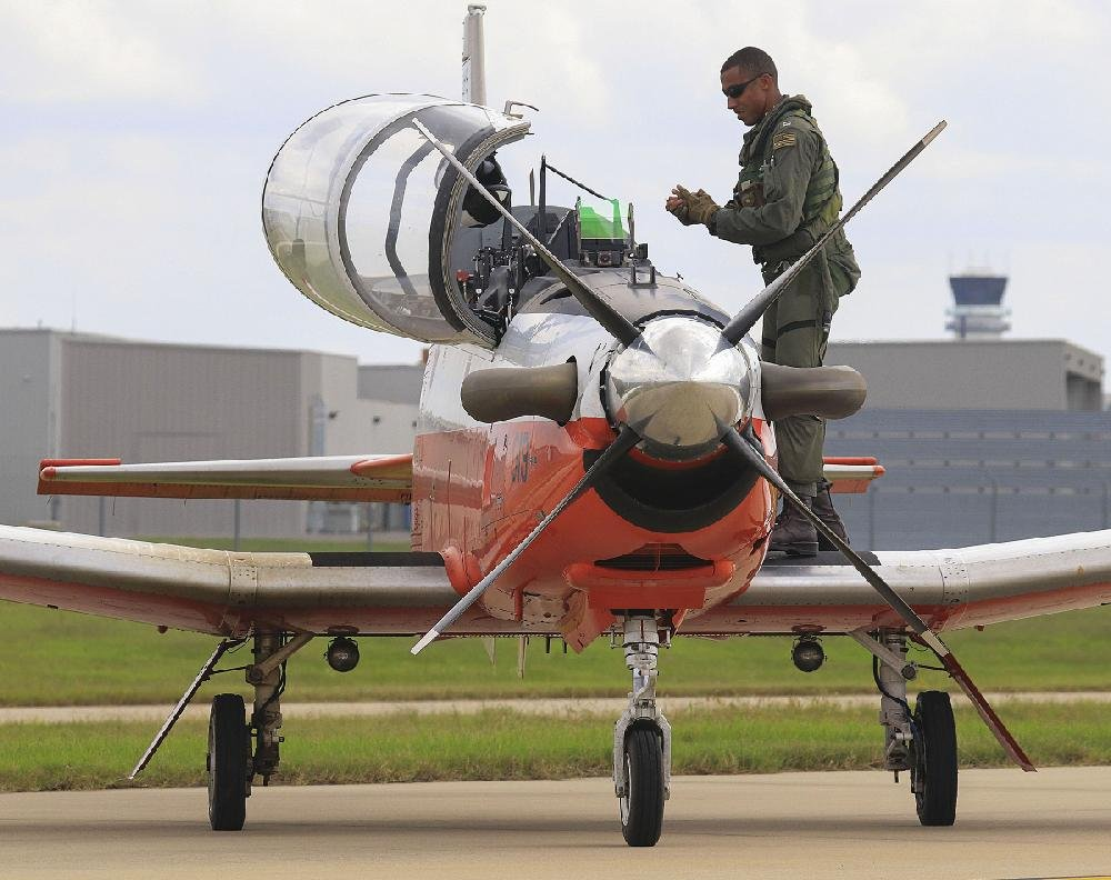 A pilot exits his T-6 Texan Navy trainer after landing Tuesday at Bill and Hillary Clinton National Airport/Adams Field. Dozens of the planes were flown in from north of Pensacola to escape Hurricane Michael.