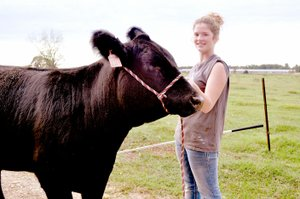 RACHEL DICKERSON/MCDONALD COUNTY PRESS Brandie Keith, 4-H member, is pictured with her Simmental heifer, Stella, which she recently showed in Tulsa.