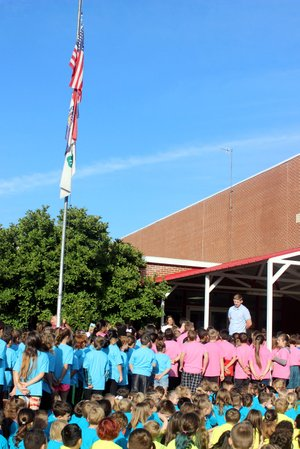 MEGAN DAVIS/MCDONALD COUNTY PRESS Eli Jones, 4-H youth program specialist, leads students at Anderson Elementary in the 4-H pledge following the first raising of the 4-H flag on campus.