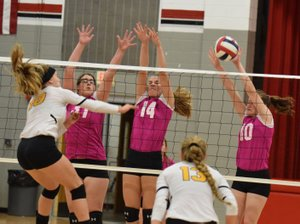 RICK PECK/SPECIAL TO MCDONALD COUNTY PRESS McDonald County's Mollie Milleson, Adyson Aanny and Katelyn Ferdig (left to right) form a triple block to stop a spike from Cassville's Sharayah Seymour during the Lady Mustangs' 25-14, 19-25, 25-17 loss on Oct. 4 at MCHS.