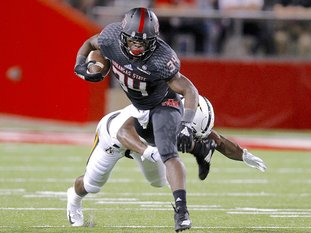 SUN FELLED: Arkansas State running back Marcel Murray (34) attempts to escape a tackle by Appalachian State defensive back Josh Thomas in the first quarter of the Red Wolves' 35-9 loss on Tuesday at Centennial Bank Stadium in Jonesboro.