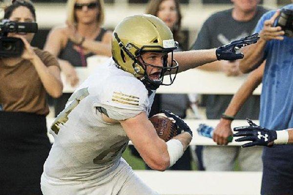 Hudson Henry, Pulaski Academy receiver, evades Cole Bowen (5), Springdale Har-Ber cornerback, Friday, Aug. 24, 2018, during the game at Wildcat Stadium in Springdale.