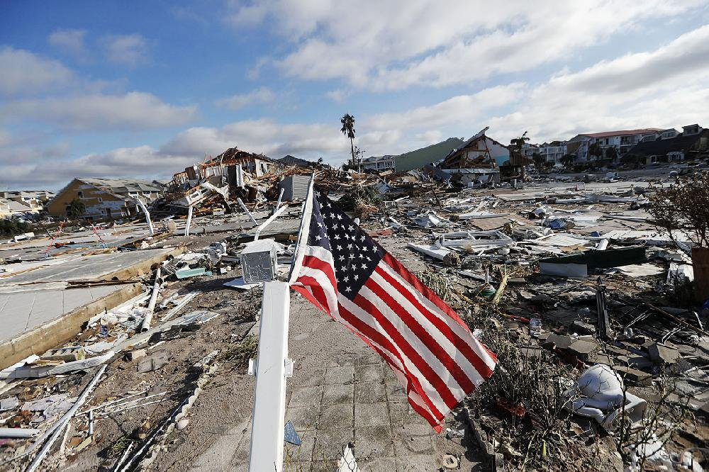 An American flag waves over what's left of a neighborhood at Mexico Beach.