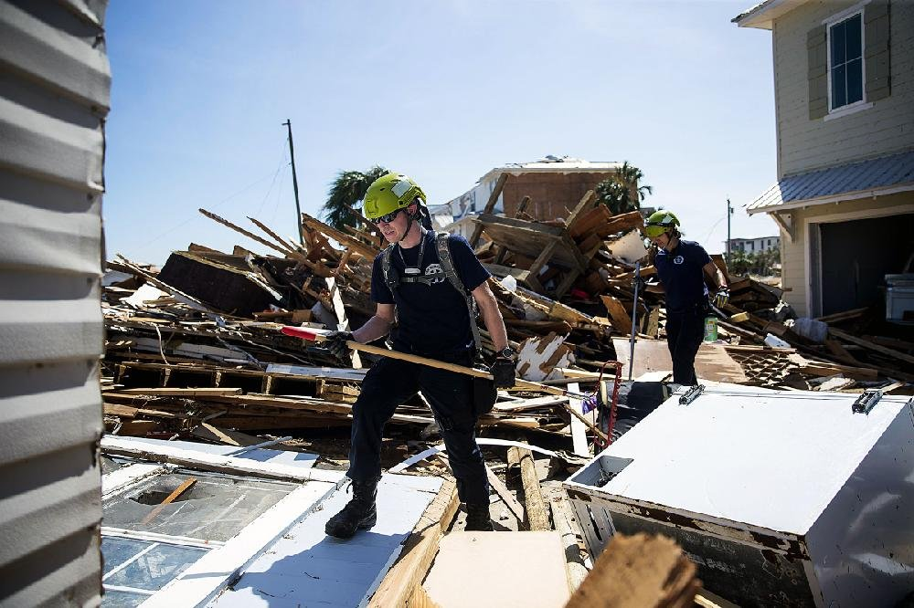 A search- and-rescue team steps through smashed homes and debris looking for survivors. Other teams were working at similar scenes of destruction across the Florida panhandle.