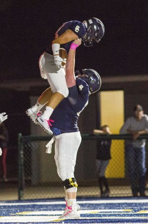 Prairie vs Shiloh Christian - Logan Kallesen (73) lifts teammate Jaret Russ (11) up in the air after scoring a touchdown against Prairie Grove at Champions Stadium, Springdale, AR on Friday, October5, 2018. Russ and the Saints are off to a 5-1 start this season. Special to NWA Democrat-Gazette/ David Beach