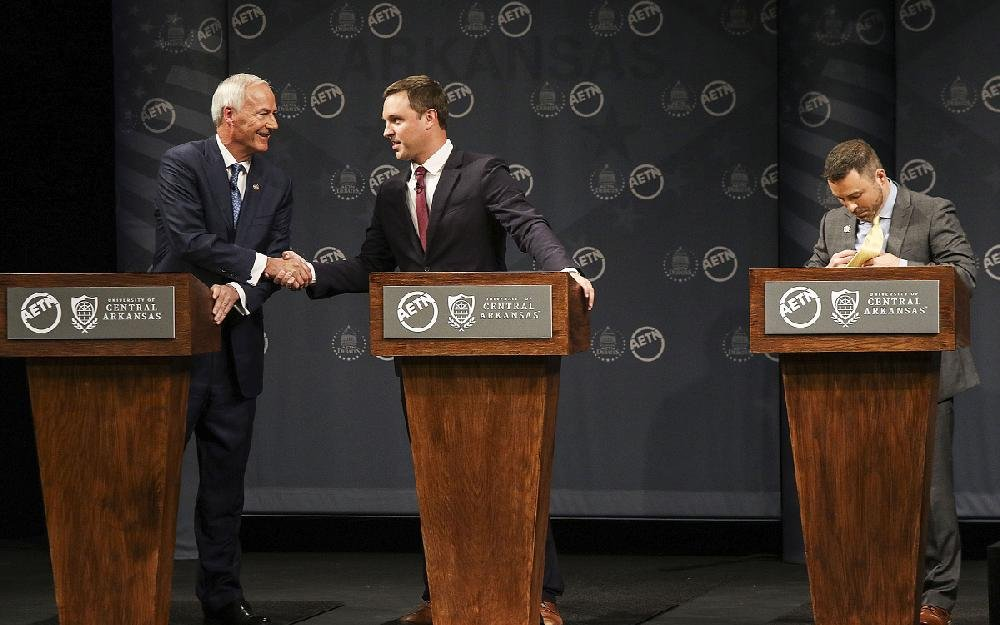 Gov. Asa Hutchinson (left) shakes hands with Democratic challenger Jared Henderson during a gubernatorial debate Friday in Conway that also included Libertarian candidate Mark West (right). Hutchinson and Henderson sparred over Hutchinson's Medicaid work requirement and Henderson's criminal-justice plan.