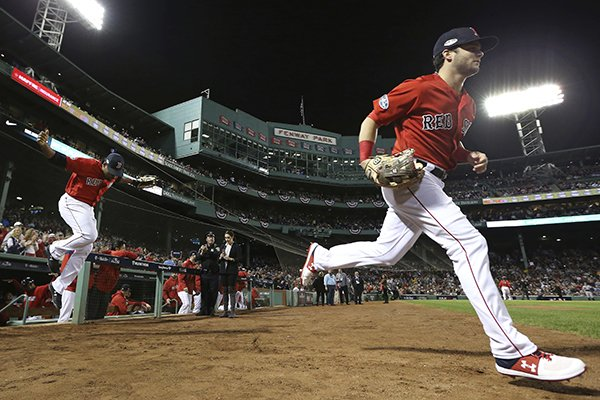 Boston Red Sox outfielders Andrew Benintendi, right, and Jackie Bradley Jr. take the field for Game 2 of the baseball American League Division Series against the New York Yankees at Fenway Park, Saturday, Oct. 6, 2018, in Boston. (AP Photo/Elise Amendola)
