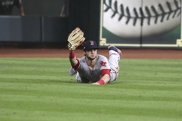 Boston Red Sox' Andrew Benintendi makes a diving catch with the bases loaded for the final out of the ninth inning against the Houston Astros in Game 4 of the American League Championship Series, in Houston, Wednesday, Oct. 17, 2018. The Red Sox defeated the Astros 8-6 to take a 3-1 lead in the series. (Barry Chin/The Boston Globe via AP)