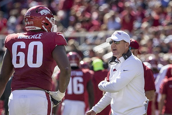 Chad Morris, Arkansas head coach, congratulates right tackle Brian Wallace and as players return to the bench after scoring an extra point in the 3rd quarter vs Tulsa Saturday, Oct. 20, 2018, at Reynolds Razorback Stadium in Fayetteville.