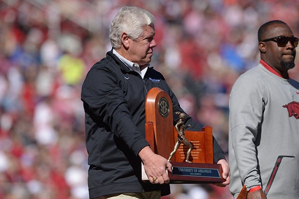 Arkansas coach Lance Harter holds an SEC championship trophy during an on-field recognition at the Razorbacks' football game against Tulsa on Saturday, Oct. 20, 2018, in Fayetteville.