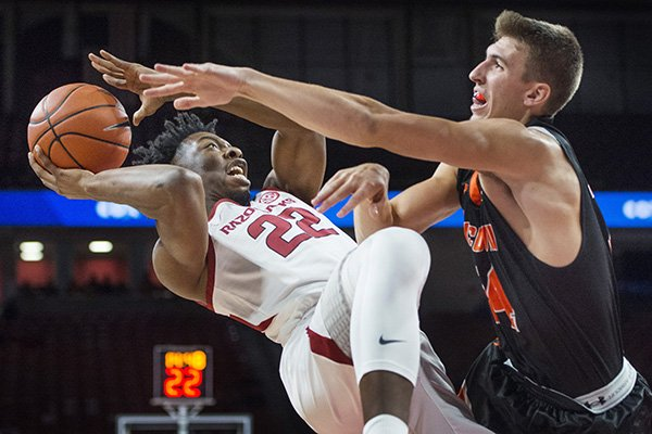 Gabe Osabuohien (22) of Arkansas attempts a shot as Caleb Hodnett of Tusculum fouls him in the first half Friday, Oct. 26, 2018, during an exhibition game in Bud Walton Arena in Fayetteville.
