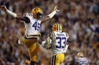 LSU safety Todd Harris Jr. (33) celebrates his interception with linebacker Michael Divinity Jr. (45) in the first half of an NCAA college football game against Alabama in Baton Rouge, La., Saturday, Nov. 3, 2018. (AP Photo/Gerald Herbert)