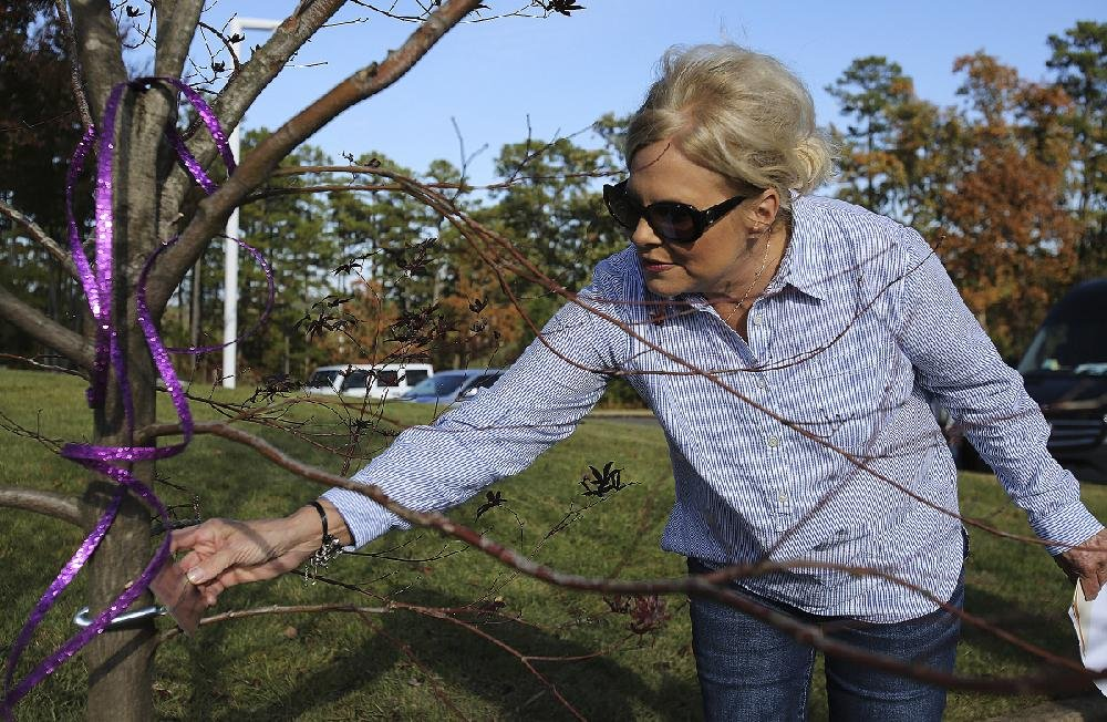 Laurie Jernigan, mother of Ebby Steppach, adjusts the plaque after the dedication ceremony for the tree planted in Steppach's honor on Sunday at Chalamont Park in Little Rock.