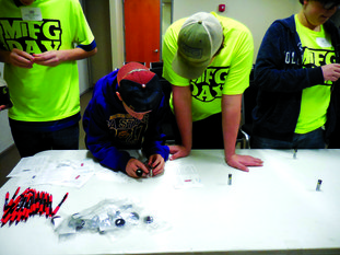 Horizontal: Students from Junction City High School work together to use a battery and magnets to trigger a coil to spin while in the break out session with Entergy representatives.