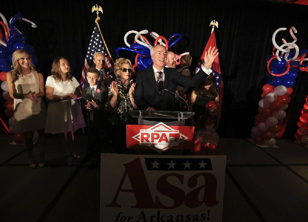 Gov. Asa Hutchinson, joined by first lady Susan Hutchinson and other family members, speaks Tuesday night at a watch party at the Embassy Suites in Little Rock.