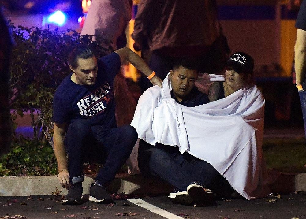 People sit near the scene of the shooting in Thousand Oaks, Calif. Survivors said patrons ran out back doors, broke windows to escape and hid in the attic and bathrooms.