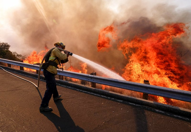 9bb20d869 A firefighter battles a fire along the Ronald Reagan Freeway