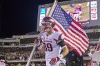 Arkansas tight end Grayson Gunter carries the American flag onto the field prior to a game against Mississippi State on Saturday, Nov. 19, 2016, in Starkville, Miss.