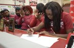 Springdale guard Marquesha Davis (right) signs a National Letter of Intent Wednesday, Nov. 14, 2018, to play basketball for Arkansas during a signing ceremony inside Bulldog Arena in Springdale.