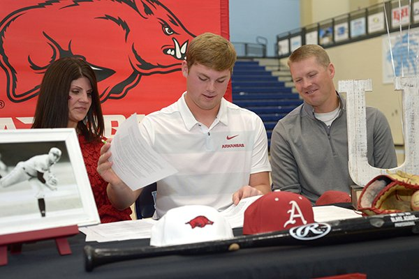 Har-Ber baseball standout Blake Adams (center) signs a National Letter of Intent Wednesday, Nov. 14, 2018, to play baseball for Arkansas while seated alongside his mother, Alicia, and father, Aaron, during a signing ceremony inside Wildcat Arena in Springdale.