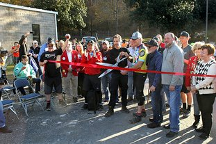 The Sentinel-Record/Richard Rasmussen TRAIL OPEN: Mayor Pat McCabe and The Walton Foundation Program Director Gary Vernon officially opened the Northwoods Trail system by cutting a ribbon at a ceremony Friday.