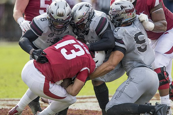 Arkansas quarterback Connor Noland is sacked by Mississippi State defenders Willie Gay Jr., Erroll Thompson and Montez Sweat during a game Saturday, Nov. 17, 2018, in Starkville, Miss.
