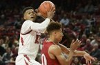 Arkansas guard Mason Jones (13) goes up for a shot against Indiana guard Rob Phinisee on Sunday, Nov. 18, 2018, in Fayetteville.