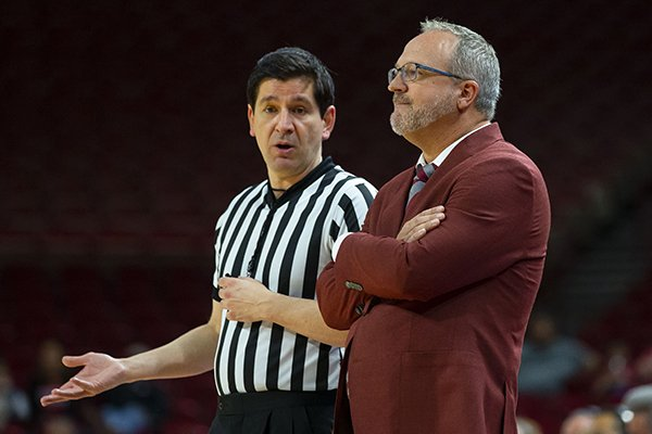 Arkansas coach Mike Neighbors (right) speaks with an official during a game against Arizona State on Sunday, Nov. 18, 2018, in Fayetteville.