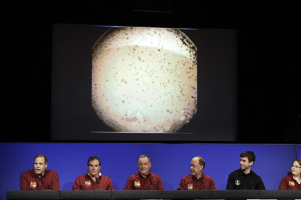 NASA officials (from left) Jim Bridenstine, Michael Watkins, Tom Hoffman and Bruce Banerdt make statements Monday under a photo sent from Mars by the InSight lander at NASA's Jet Propulsion Laboratory in Pasadena, Calif.