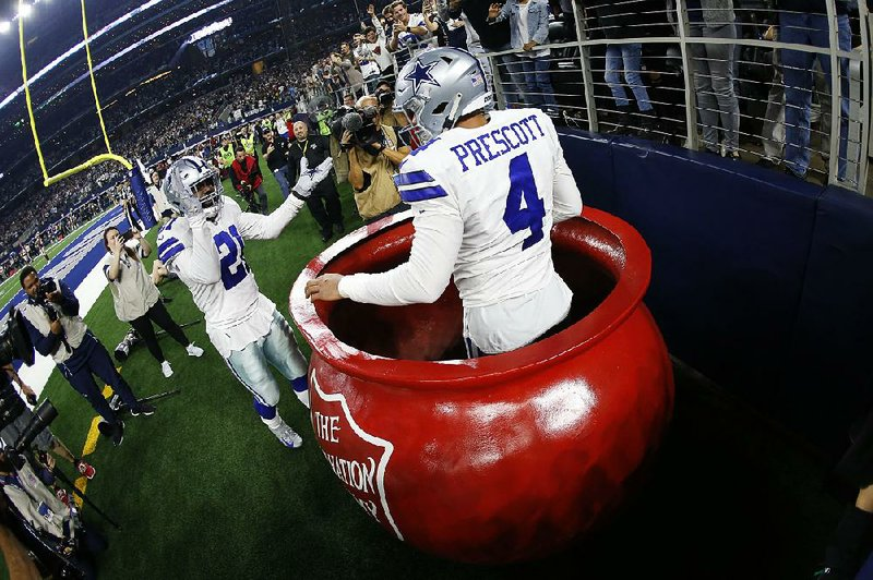 8afb9ac177b19 ... into a Salvation Army kettle by running back Ezekiel Elliott following  his touchdown against the Washington Redskins on Nov. 22 in Arlington
