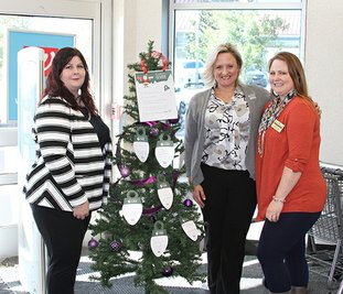 The Sentinel-Record/Tanner Newton SENIOR TREE: From left are Christina Godfrey, Jennifer Bassett and Kandy Gould of Home Instead with one of the Be a Santa to a Senior program's trees at Walgreens. The tree is covered in ornaments bearing the names and wish lists of local seniors who do not have families nearby to be with during the holidays.