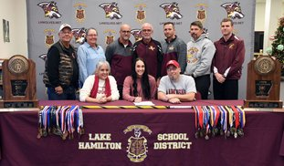 The Sentinel-Record/Grace Brown HOG SIGNING: Lake Hamilton senior Edie Murray, center, signs a letter of intent with the University of Arkansas' track and field program Wednesday at Lake Hamilton High School. Murray is accompanied in front by her mother, Darbi Murray, left, and father, Todd Murray; and back, from left, grandparents, Sue and Billy Murray; and coaches Morry Sanders, Karl Koonce, Brandon Starr, Lewis Hunt and Brandon Smith.