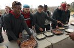Mike Woods (from left), Isaiah Nichols and Devwah Whaley join other members of the University of Arkansas football team Thursday, Dec. 6, 2018, in serving a meal at the 7Hills Homeless Center's day center in Fayetteville. Members of the team served food at several locations around Northwest Arkansas including Arkansas Children's Hospital Northwest, Mercy medical center in Rogers and the Boys and Girls Club of Fayetteville.