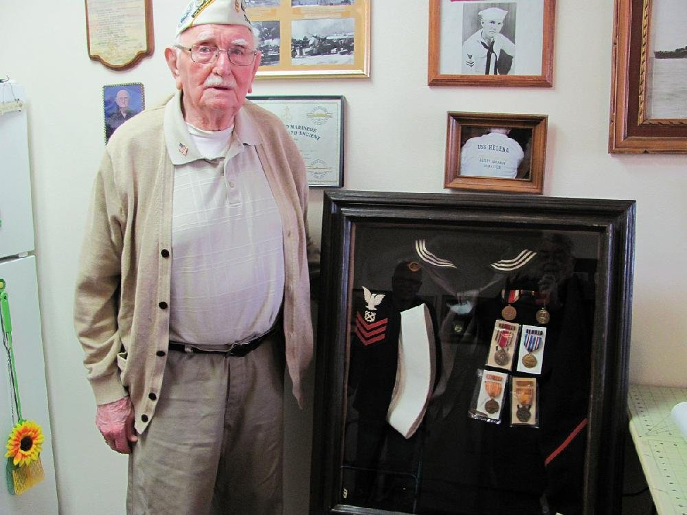 Harold Mainer of Fort Smith, who was at Pearl Harbor when the Japanese attacked on Dec. 7, 1941, shows the uniform he wore and the medals he was awarded for service aboard the USS Helena during the war. A photo of a young Mainer on the wall above the display was taken after the light cruiser Helena was sunk in battle in July 1943.