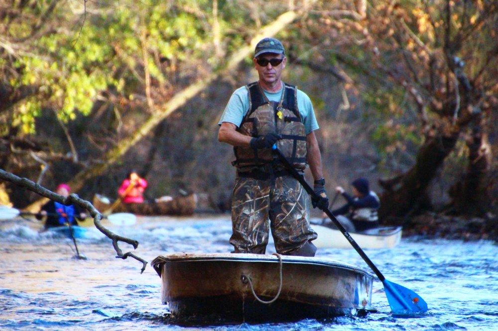 Cowper Chadbourn paddles a barely seaworthy fiberglass boat found twisted and trashed among trees — the prize for the day during an Arkansas Canoe Club Black Ops Advanced Trash Removal outing Nov. 24 on Cadron Creek. (Special to the Democrat-Gazette/BOB ROBINSON)