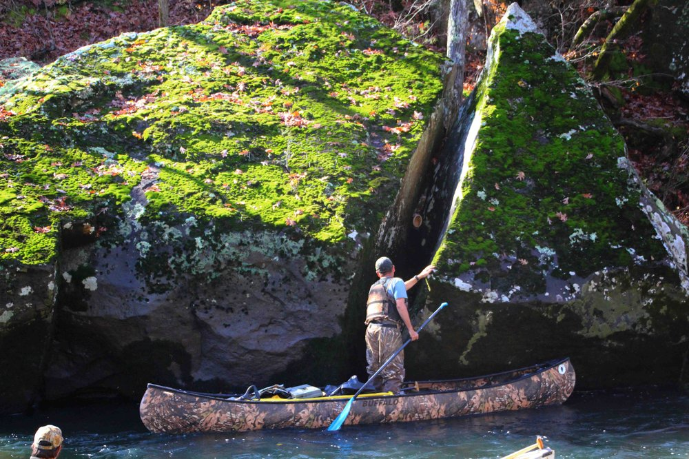 Cowper Chadbourn figures out a way to retrieve a plastic bucket lodged between giant boulders. (Special to the Democrat-Gazette/BOB ROBINSON)