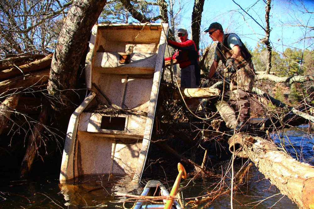 Roger Head (left) and Cowper Chadbourn work at dislodging a trashed boat from its nest in downed trees. (Special to the Democrat-Gazette/BOB ROBINSON)