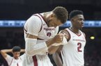 Arkansas forward Daniel Gafford (left) walks off the floor with teammate Adrio Bailey (2) after missing a shot as time expired during a game against Western Kentucky on Saturday, Dec. 8, 2018, in Fayetteville.