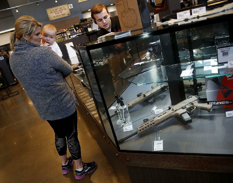 70c69fd4788 A salesman points out features on a handgun for Anne Vifquain while she  holds her son Gavin at the Frontier Justice store in Lee s Summit