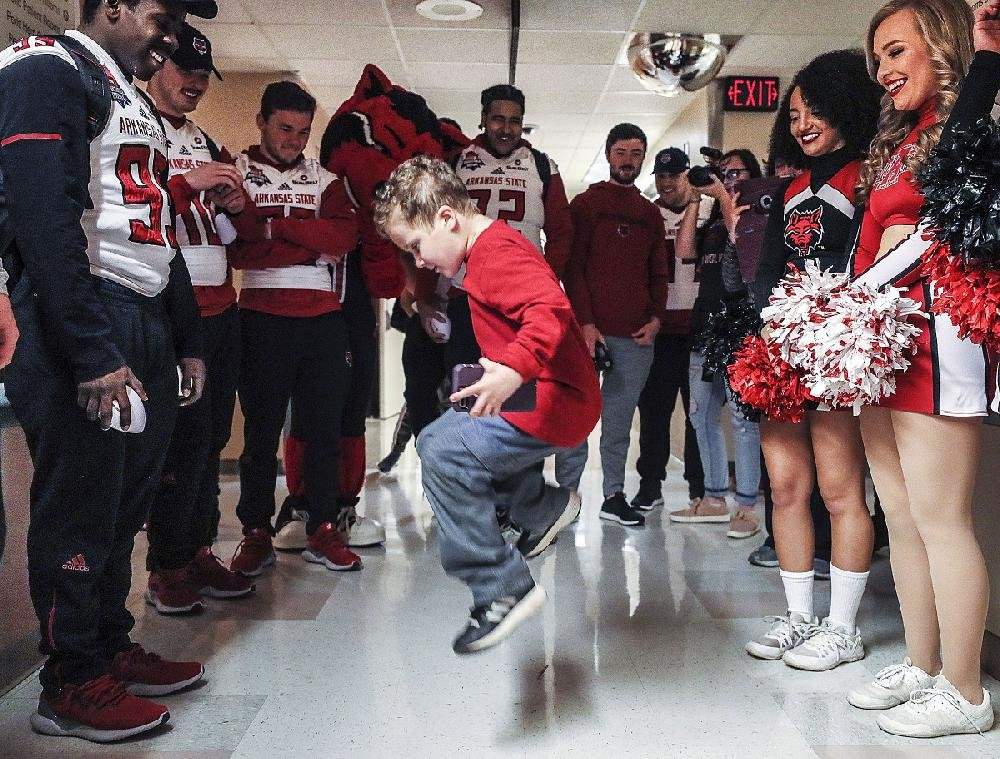 Mason Roberts, 6, of Sierra Vista, Ariz., takes some time out of his leukemia treatment Thursday to dance for Arkansas State football players and cheerleaders during the Red Wolves' visit to Diamond Children's Medical Center in Tucson, Ariz.