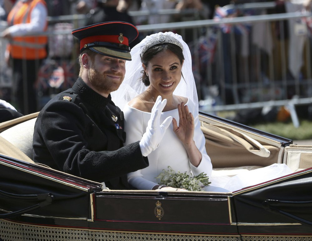 In this May 19 file photo, Britain's Prince Harry and Meghan Markle ride in an open-topped carriage after their wedding ceremony at St. George's Chapel in Windsor Castle in Windsor, near London, England. (Aaron Chown/pool photo via AP)