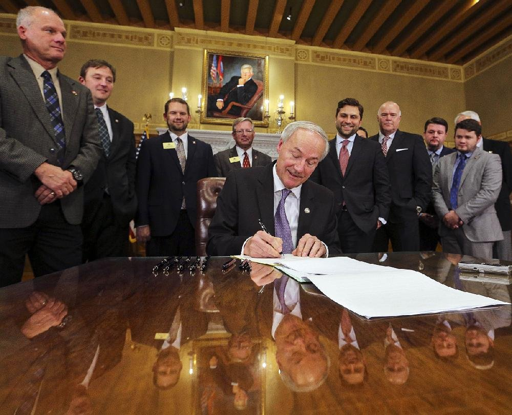 Gov. Asa Hutchinson signs a law in February 2017 cutting the income tax rate for Arkansans making less than $21,000 a year.