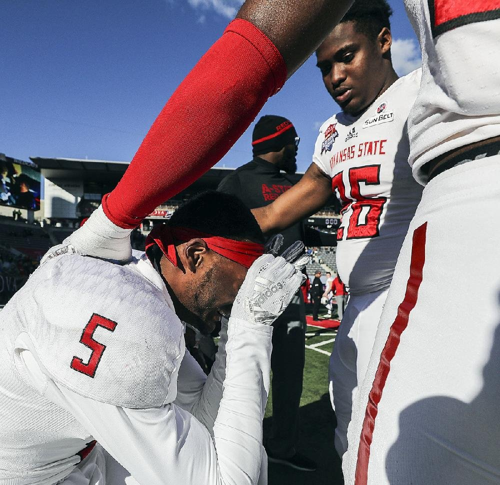 Arkansas State's Kendrick Edwards (5) is consoled by teammates after the Red Wolves' loss to Nevada. For more photos, go to arkansasonline.com/galleries.