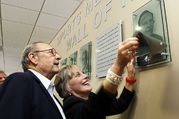 Former Arkansas Democrat-Gazette and Arkansas Gazette sports writer Jim Bailey (left) and Brenda Scisson admire Bailey's picture during a ceremony adding him to a sports members Wall of Fame in the War Memorial Stadium press box in 2010. Bailey, 86, died in his home Wednesday evening.